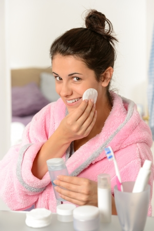 cotton pad: Young smiling woman cleaning face with cotton pad Stock Photo