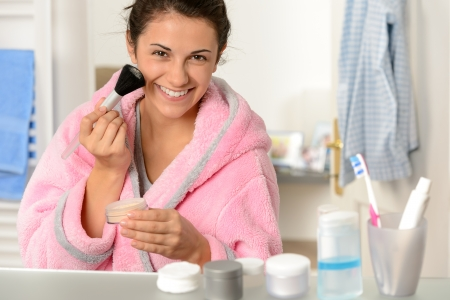 Young woman applying face powder with brush in the bathroom Stock Photo - 18854972