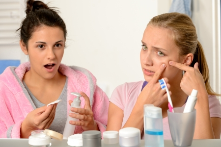 Young teenager with acne problem in the bathroom with friend photo
