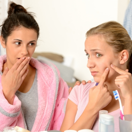 Young teenager and her friend squeeze pimple in the bathroom Stock Photo