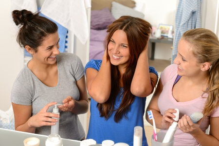Three laughing teenager girls talking in the bathroom together