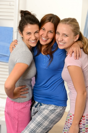 Three teenage girls friends laughing in pajamas together photo