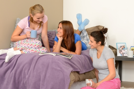 Three teenage girls talking at pajama party in bedroom
