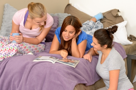 Three teenage girls reading at slumber party in pajamas photo