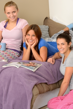 Three teenager girls lying on bed reading magazine photo