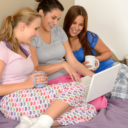 pajamas: Three cheerful girls surfing on the net on laptop