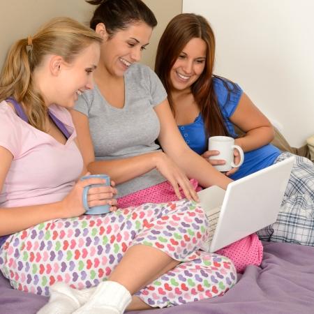 net surfing: Tre ragazze allegre navigazione in rete sul computer portatile Archivio Fotografico
