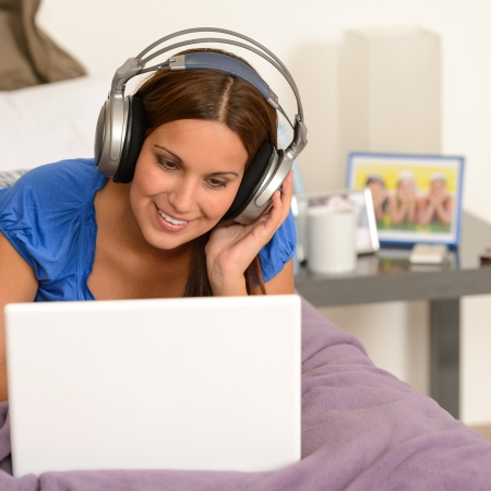Teenage girl surfing on internet with laptop and headphones photo
