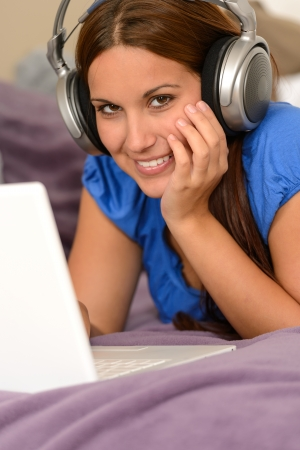 Young smiling girl using laptop and listening music with headphones Stock Photo - 18853459