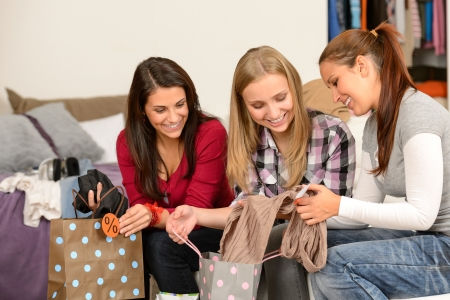 Three cheerful girls with clothes from sale shopping bags Stock Photo - 18853460