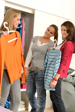 woman closet: Three teenager girl friends choosing clothes from closet together Stock Photo