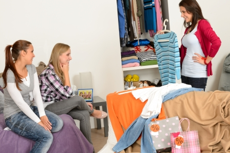 Young girl showing shirt to friends after shopping