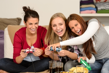 Laughing young girls playing with video games at home
