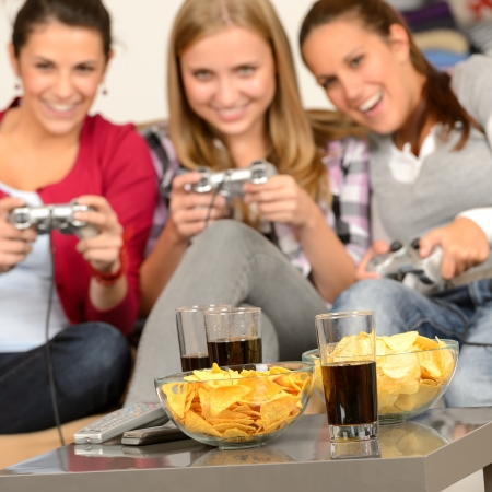 weekend activities: Smiling teenage girls playing with video games with potato chips