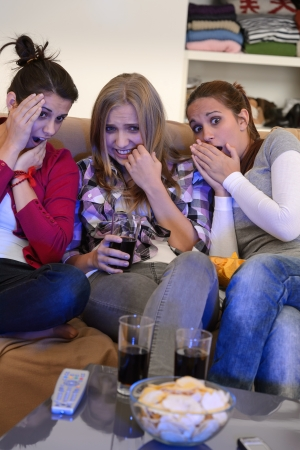 Scared young girls watching horror movie on television photo