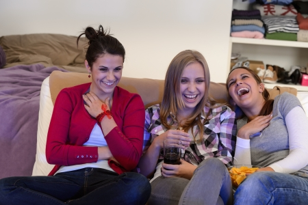Laughing young girls watching TV together sitting on couch photo