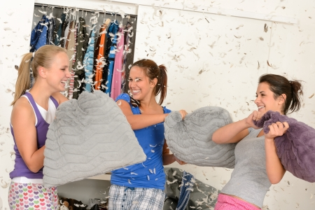 sleepover: Young laughing girls during pillow fight with flying feathers