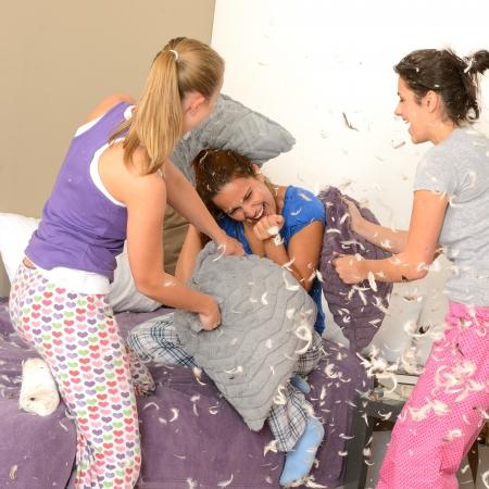 pijama: Niñas adolescente almohada lucha en el dormitorio con plumas volando Foto de archivo