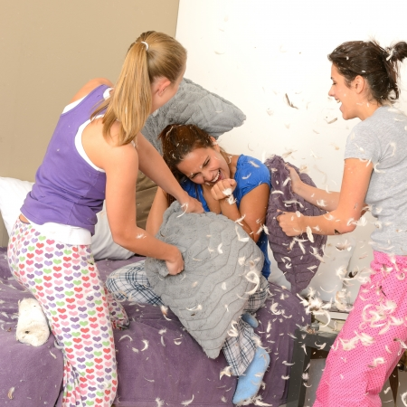 sleepover: Teenager girls pillow fighting in bedroom with flying feathers