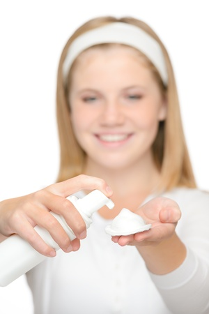 Cheerful teenager girl using cleaning foam cream moisturizer Stock Photo - 18969702