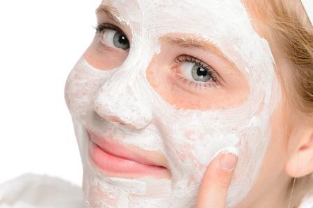 pulizia viso: Giovane ragazza sorridente applicare la pulizia del viso maschera di bellezza di trattamento