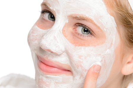 Young smiling girl applying cleaning facial mask treatment beauty