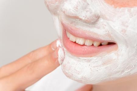 pulizia viso: Ragazza sorridente che mette maschera facciale dita pulizia trattamento di bellezza Archivio Fotografico