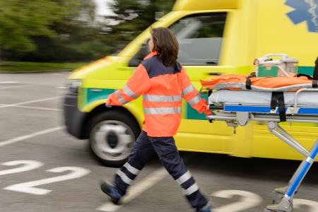 Blurry paramedics in hurry pulling gurney next to ambulance car Stock Photo - 19420713