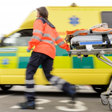 Running blurry paramedic woman rolling stretcher outside of ambulance car Stock Photo