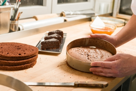 Cook taking out layer cake from cake form Standard-Bild
