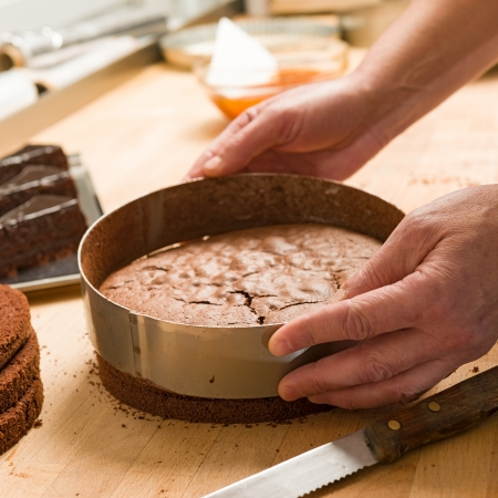 pound cake: Cook taking out layer cake from cake form Stock Photo