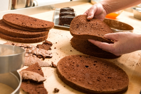 slicing: Chef cutting chocolate cake layers and stacking them