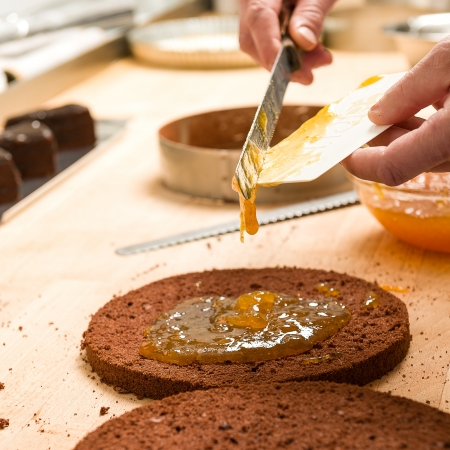 Cook making layer chocolate cake with orange marmalade photo