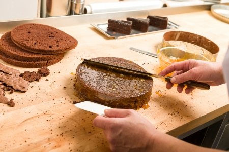 Cook spreading sauce on cake with knife in kitchen Stock Photo