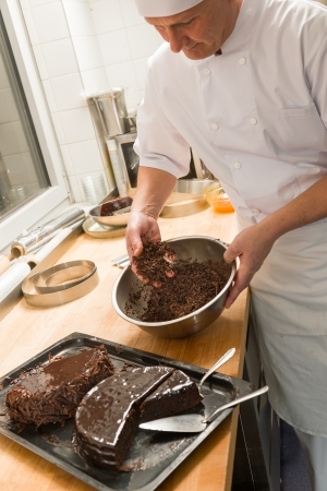 adding: Cook adding chocolate sauce with hands to cake in kitchen Stock Photo