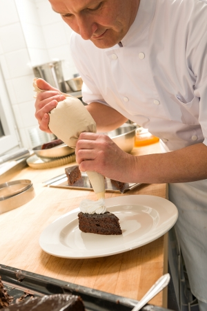 Pastry chef decorating cake with frosting in the kitchen photo
