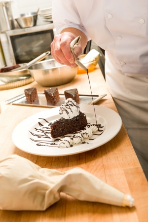 Male cook decorating slice of chocolate cake with sauce photo