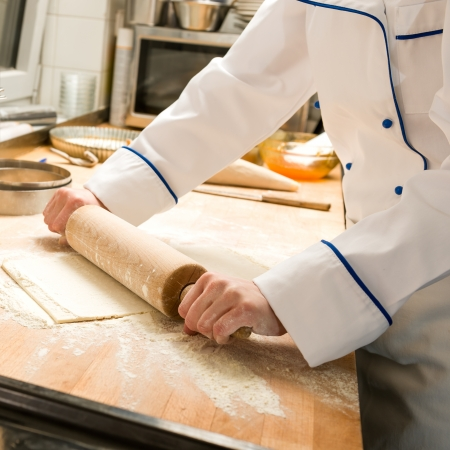Cook rolling dough in kitchen with rolling pin and flour photo