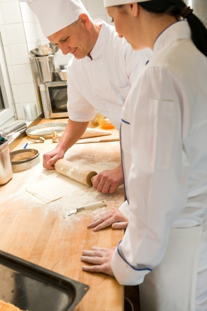 Male chef rolling dough with rolling pin assistant watching photo