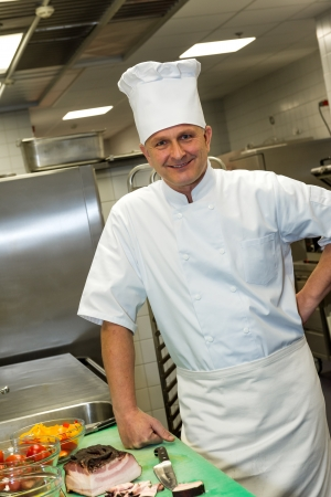 commercial equipment: Smiling male chef posing in commercial kitchen interior
