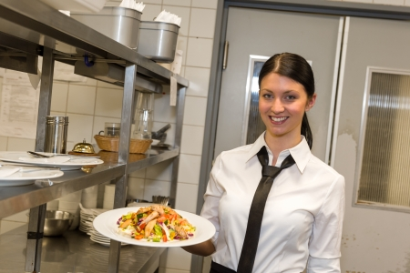 Smiling waitress serving salad on plate in restaurants kitchen photo