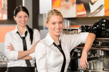 with coffee maker: Two waitresses posing in coffee house in uniform