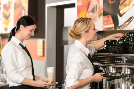 Two waitresses serving coffee with machine in shop photo