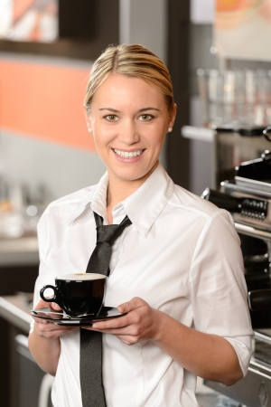 Young smiling waitress posing with cup of coffee