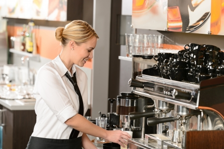 barista: Smiling waitress preparing hot beverage in coffee house