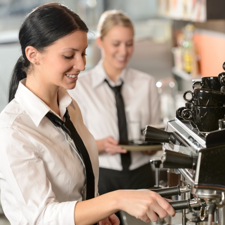 barista: Joyful female barista operating coffee maker machine in coffee shop