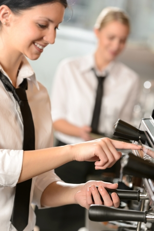 Smiling women waitress preparing coffee with machine Stock Photo - 19379843