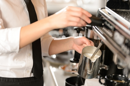 with coffee maker: Barista steaming milk for hot cappuccino with machine