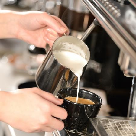capuchino: Manos Waitress vertiendo leche en la preparación del capuchino