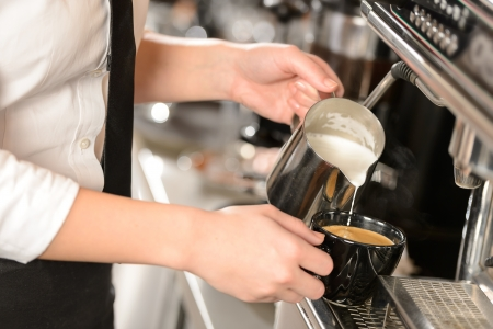 Waitress hands pouring milk making cappuccino photo
